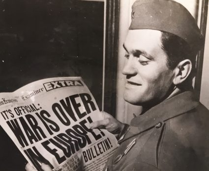 Vladimir Dedijer reads the newspaper headline: 'The War is Over'. (IWM, London, photographic archive)