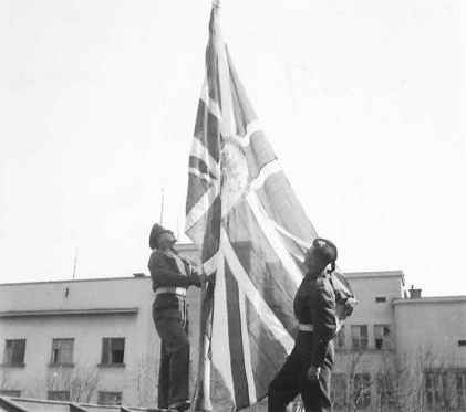 The British Embassy flag is raised for the first time since the mission was reopened in Belgrade on 24th March 1945. (IWM, London, photographic archive, NA23376)