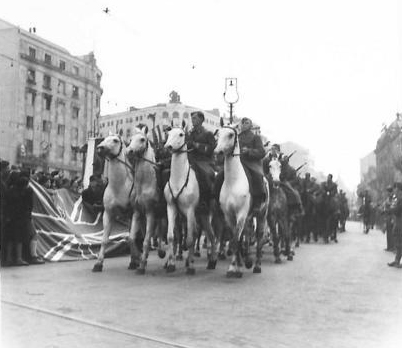 Crowds with Union Jack flags cheer NOVJ soldiers on horseback in Republic Square 27th March 1945. (IWM, London, photographic archive, NA23617)